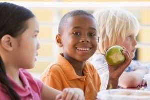 Kindergarten children eating lunch smiling at camera