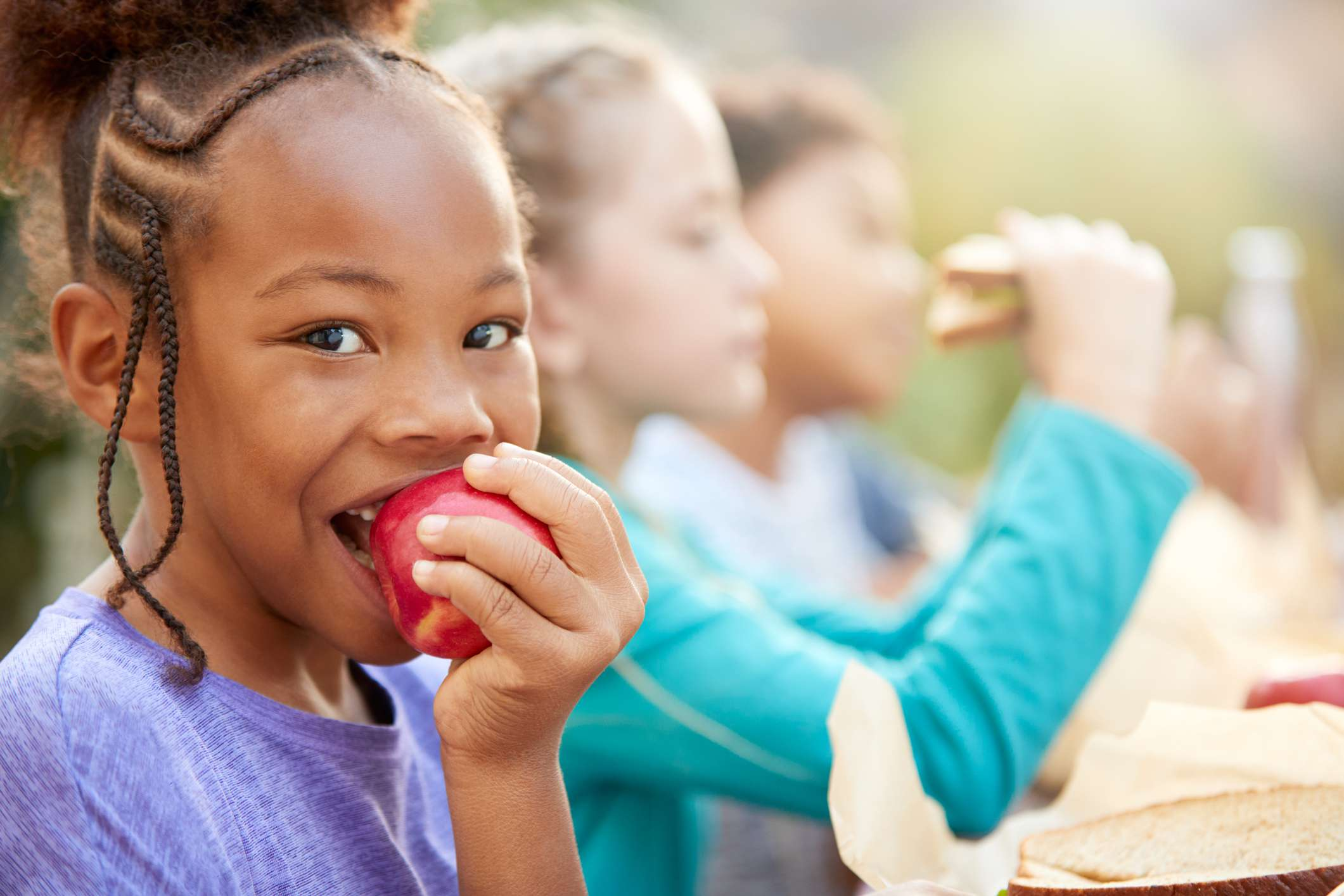 Girl With Friends Eating Healthy Picnic At Outdoor Table In Countryside